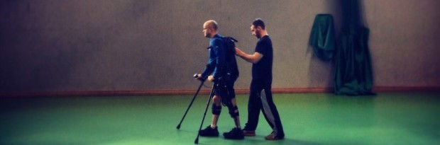 robotic exoskeleton helping someone to walk with assistance from another person