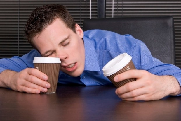stay home: male office worker with falling asleep with coffee cups in both hands