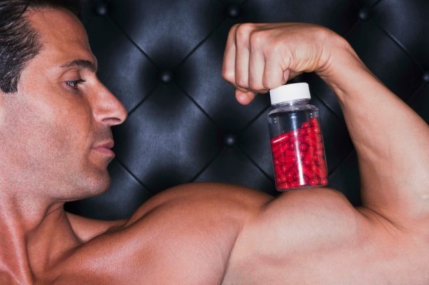 libido: man with a giant bicep staring at pill bottle