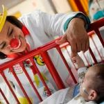 A baby grabs the finger of a member of 'Laughter Doctors of Ciudad Juarez' as she performs at a children's hospital in Ciudad Juarez March 11, 2015. Through clown performances, music and interactive activities, the group of doctors visit different hospitals throughout the border city, using laughter to help aid the recovery of young and elderly patients suffering from serious illness or injury, as well as provide hope for the hospitalized patients and their families, local media reported. Picture taken March 11, 2015. REUTERS/Jose Luis Gonzalez (MEXICO - Tags: SOCIETY HEALTH) - RTR4T5X9