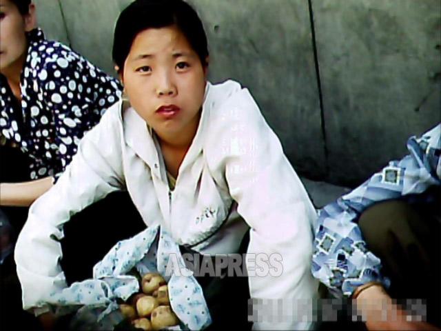 やはり中心部の牡丹江区域のアパート街も座りんこんで商売をする人たちで賑わう。写真はジャガイモを売る若い女性。2011年7月 撮影ク・グァンホ(アジアプレス)