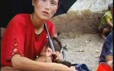 젖먹이를 데리고 노상에서 떡이나 빵을 파는 여성. 양산과 화장은 잊지 않는다. 2007년 황해북도 사리원시에서 촬영. (아시아프레스)