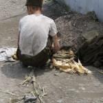 뒷모습의 셔츠에 비친 갈비뼈가 애처롭다. 옆에는 후줄근한 군복과 군모가. 2008년 8월 평양시 외곽에서. 촬영 장정길(아시아프레스)
