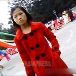 조금 구겨진, 그래도 예쁘장한 붉은 코트를 입은 여중생. 노동당 창건 기념 행사 연습에 학생들이 멋을 내고 모여들고 있다. 2013년 10월 양강도 혜산시에서. 촬영 아시아프레스