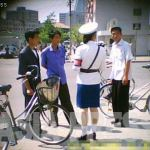 """These three men were stopped at an intersection and reprimanded for riding their bicycles in an illicit manner. Usually, when detaining a citizen, the officer starts by confiscating his or her identification card. This move prevents resistance and ensures obedience most of the time. Citizens typically resort to the fastest and easiest way of resolving the problem: bribery. The """"price"""" was around 500 won (12 U.S. cents) at the time this photo was taken. [Gu Gwang-ho, 2011]"""
