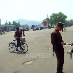 A military policeman is checking certificate of a pedestrian at Pyongsung City of South Pyongan Province on August 2009. Taken by Kim Dong-cheol (ASIA PRESS)