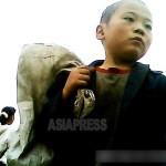 "A boy roaming around a city with a big cloth bag. The photographer said that, ""He may have escaped from a detention center for orphans since his hair is entirely shaved off.""  September 2013, in Pyongsong City, South Pyongan Province.  Taken by ASIAPRESS."