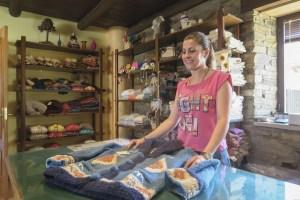 Noelia, muestra una chaqueta de lana confeccionada en la empresa de artesanía textil Santiago Geijo de Val de San Lorenzo. / EDUARDO MARGARETO