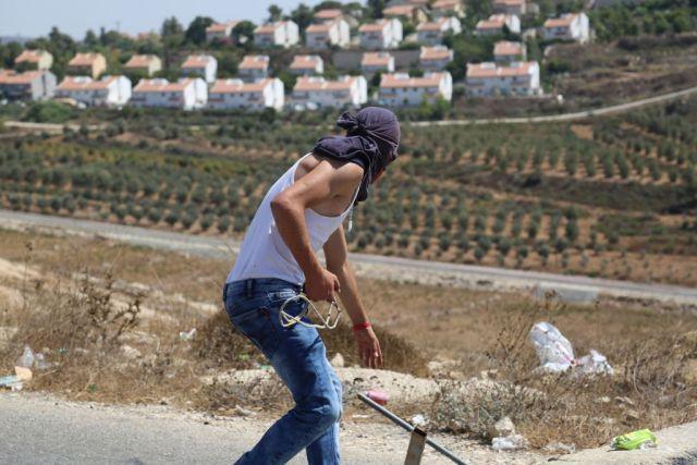Ein palästinensischer Jugendlicher aus dem Dorf Nabi Saleh macht sich bereit Steine auf IDF-Soldaten zu schleudern. 28. August 2015. Foto Eric Cortellessa / Times of Israel