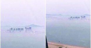 海面上霧氣籠罩,一棟棟高樓聳立其中,燈火閃爍,山脈連連。(網路圖片)
