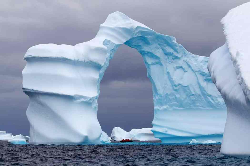 Huge Arch Shaped Iceberg in Antarctic waters with a boat in the distance