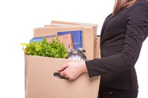 Side view. Business woman holding box with office items. isolated on white background.