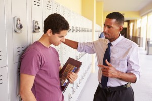 Male teacher counselling young man