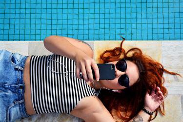 Age of the Customer: Frau liegt mit Handy und Kopfhörer im Ohr am Swimmingpool.