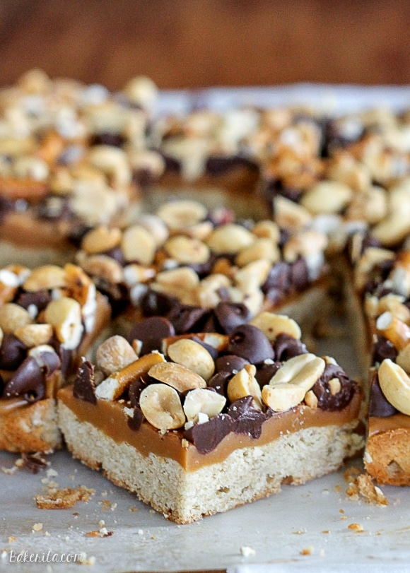 These Fully Loaded Bars have an oat shortbread crust topped with peanut butter caramel, pretzels, chocolate chips, and roasted peanuts. They're irresistible!