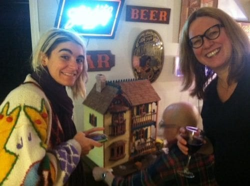 "Garcia de la Huerta and Fredrick pose at a potluck, in front of their host's dollhouse, which provided further inspiration for the artist consumed by ""memory."""
