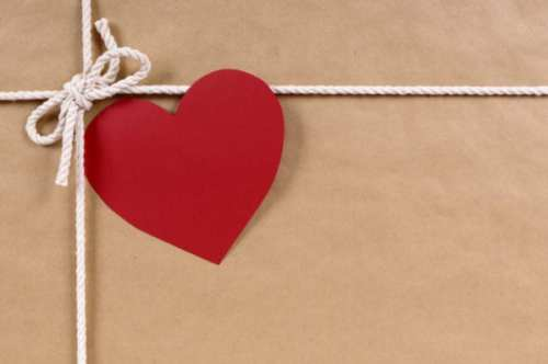 Brown paper package or gift with red heart shape valentine card.