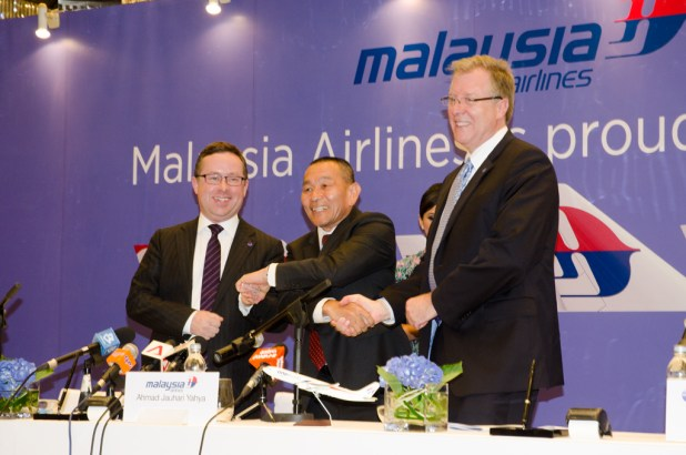 Alan Joyce, Ahmad Jauhari Yahya, and Bruce Ashby, celebrate after signing the contract