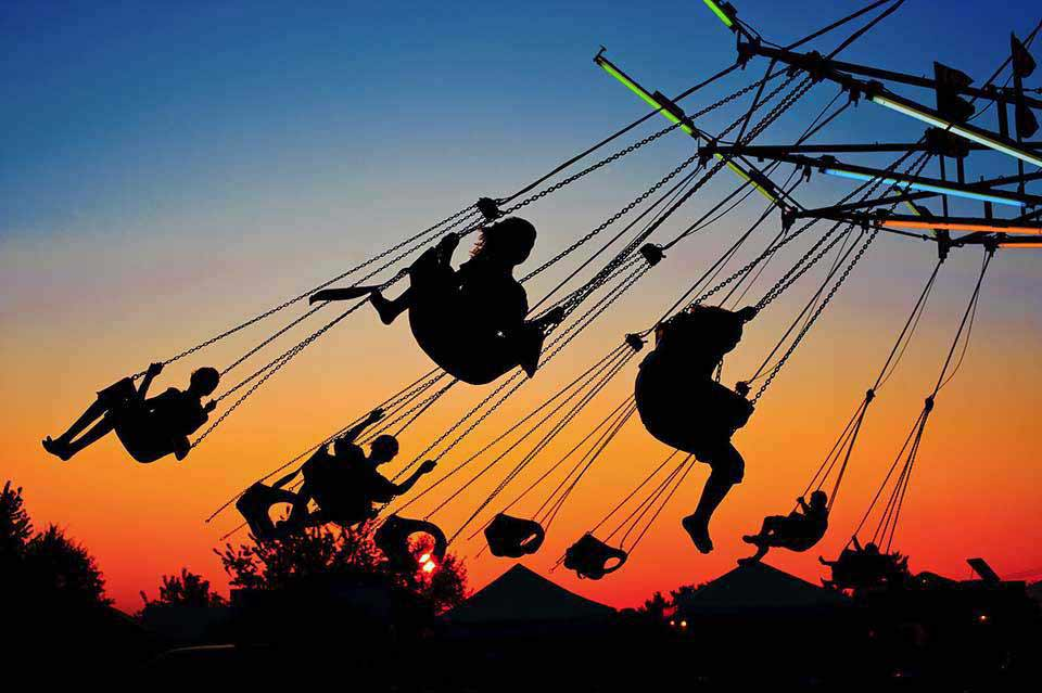 Home page for image for Barry Kidd Photography, a commercial and corporate photography service, is a silhouette of children on carnival swings at sunset.
