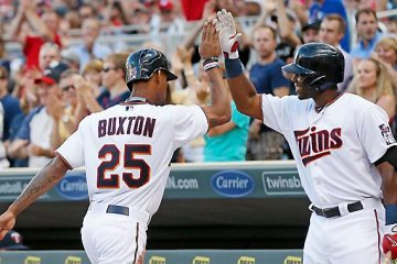 Minnesota Twins' Torii Hunter, right, congratulates Byron Buxton after he scored on a single by Brian Dozier in the first inning Monday, June 22, 2015, at Target Field in Minneapolis. (AP Photo/Jim Mone)