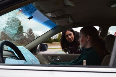 Witness Trisha Sharp peers within the damaged vehicle to make sure passenger Sally Rider was okay after the accident.