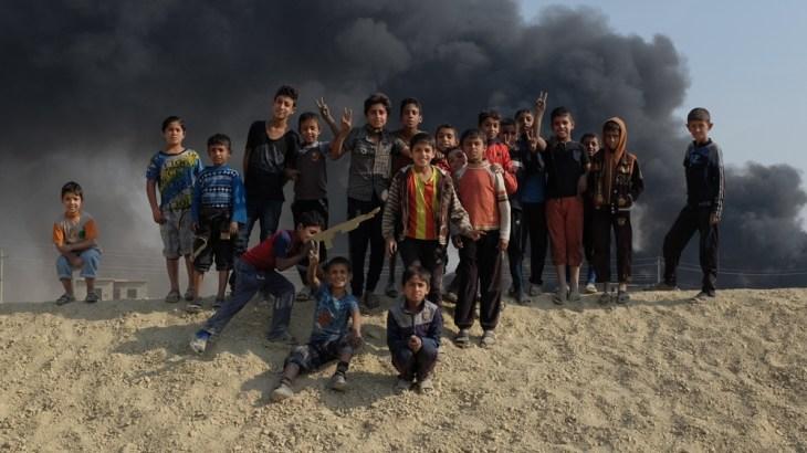 Children playing around a oil wells on fire in Qayyara, Iraq