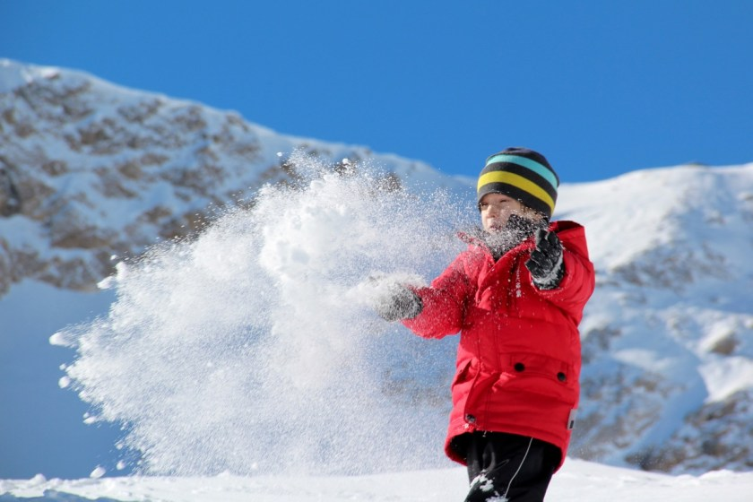 Skigebiete für Familien: Weißer Pulverschnee, das Glitzern der Sonne auf dem Berggipfel und glückliche Kinder mit kalten Nasenspitzen und roten Wangen.