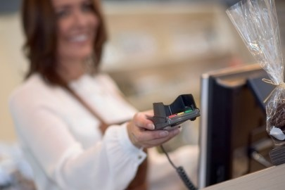 A smiling service worker offering a credit card terminal to a customer. Blurred face, focus on credit card register.
