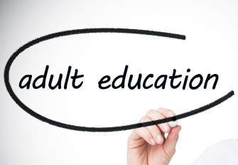 Businesswoman writing the words adult education