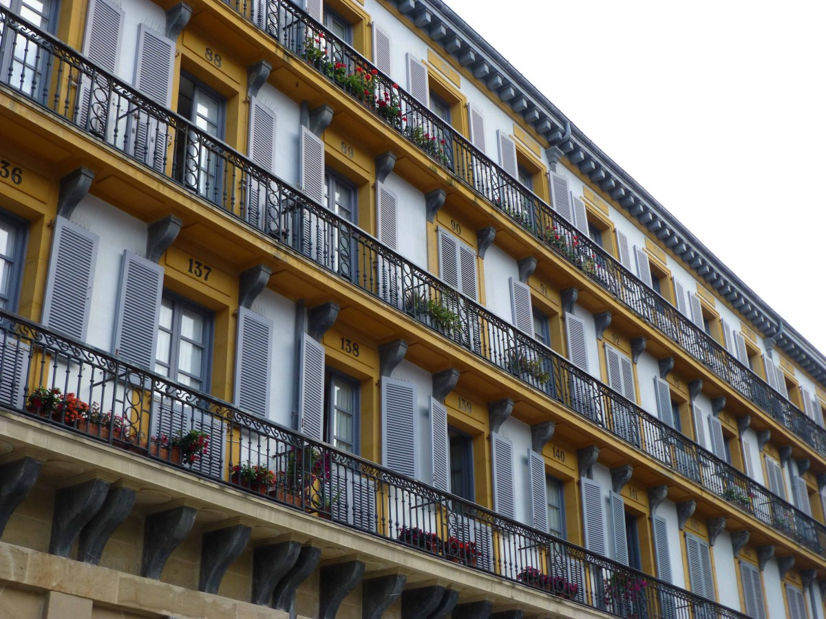 Photograph of yellow building windows and balconies in San Sebastian, Basque Country, Spain.