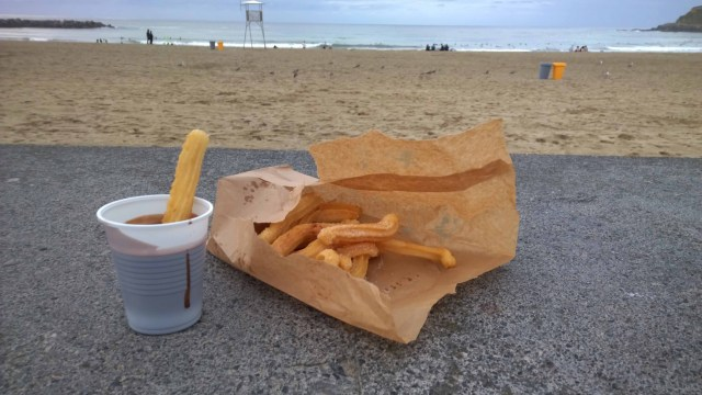 Photograph of churros in a brown paper bag and chocolate sauce in a plastic cup on a wall overlooking San Sebastian beach and sea.