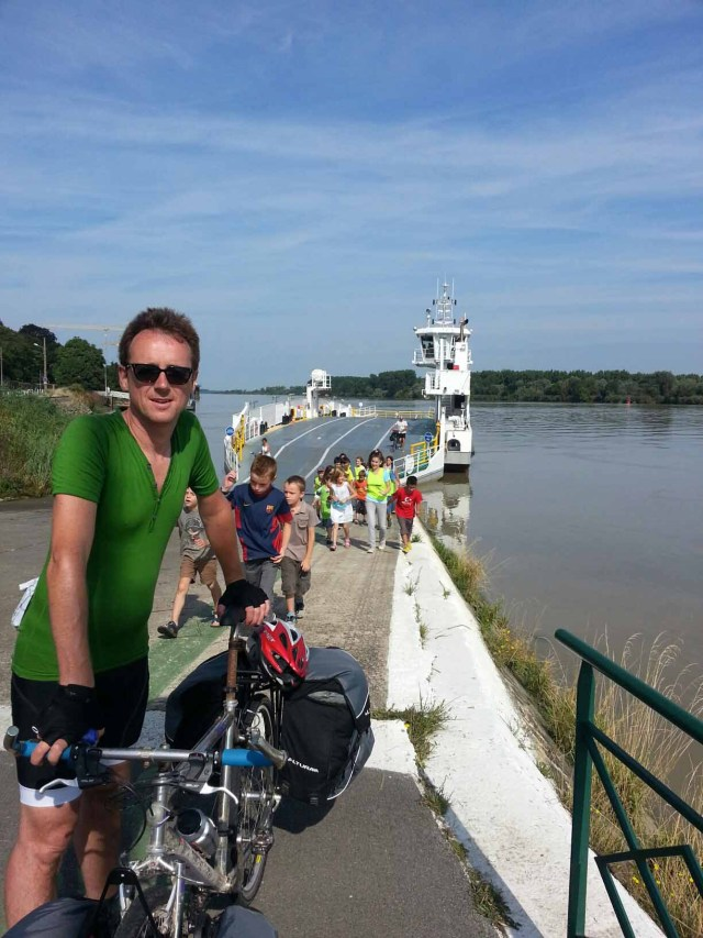 Photograph of Keith and his bicycle with the Loire River ferry and some children in the background.