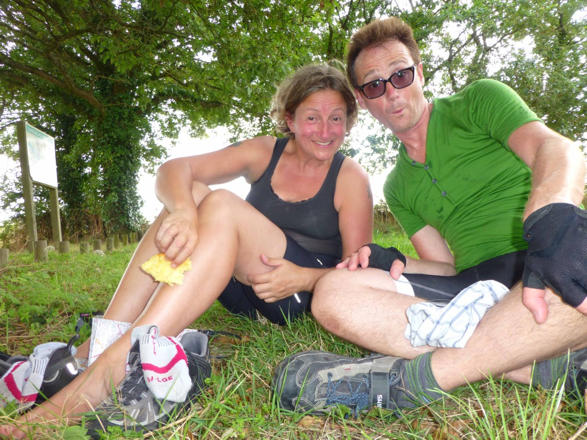 Photograph of Sarah and Keith sitting on the grass looking red-faced and exhausted after cycling.