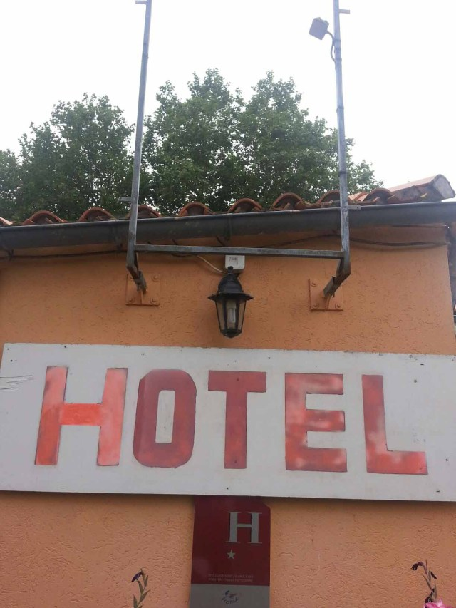 Photograph of a sign saying 'Hotel' on the side of a tatty building.