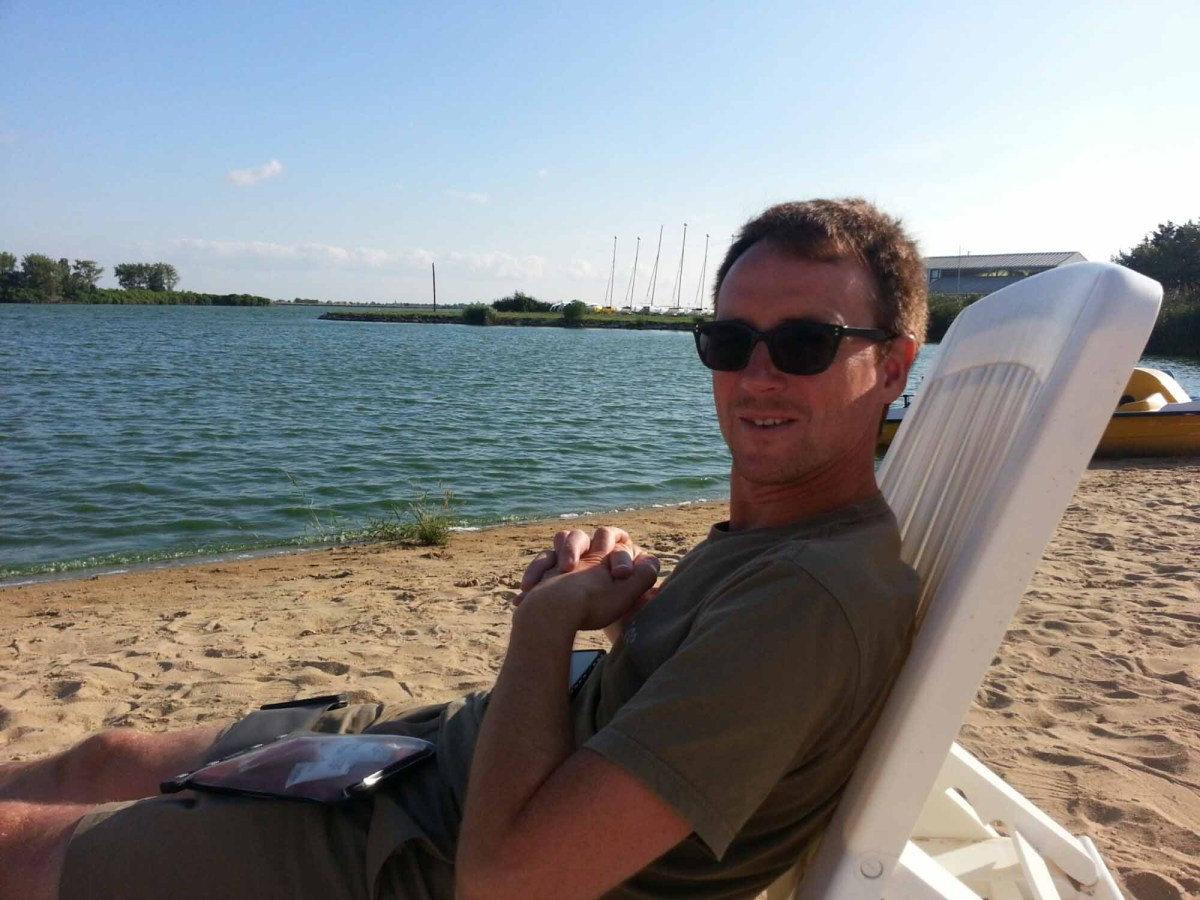 Photograph of Keith sitting on a sunlounger on a sandy river beach in Lucon, France.