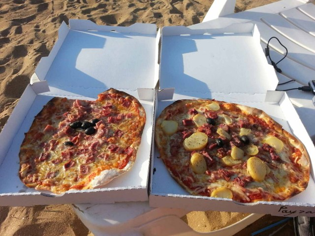 Photograph of two pizzas in boxes side by side.