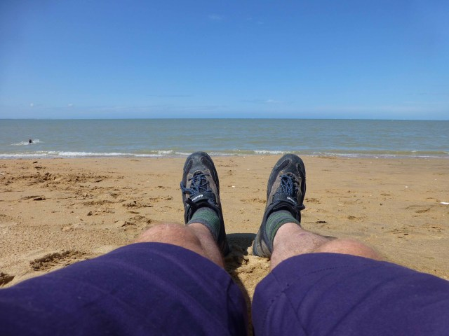 Photograph of Keith's legs and feet on a sandy beach with the sea in the background
