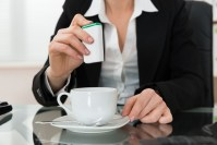 Close-up Of Businesswoman Putting Sugar In Cup