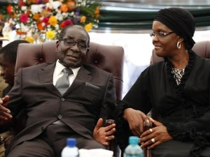 Zimbabwe President Robert Mugabe (L) speaks to his wife Grace during the funeral of his sister, Bridget, in the village of Zvimba, 90 km (55 miles) west of Harare January 21 2014.      REUTERS/Philimon Bulawayo
