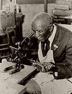 Carver looking through a microscope in his lab