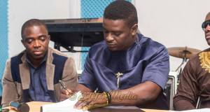 Kumi Guitar with Sammy Flex looking on as he signs the contract