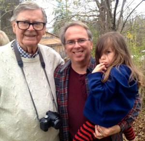 Photo By Woody Greenberg : Earl Hamner, Jr. and BRL Publisher Tommy Stafford (along with a pouty Peyton Stafford) stop for a shot on the front sidewalk of Hamner's boyhood home in Schuyler in April 2014. He was back in his hometown during the filming of a biography on his life. Hamner wrote for many columns for this very magazine in our early days as well.