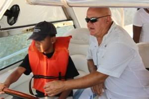 Dan Bradbary assists Zavion Hayes, 9, with driving the boat along the Intracoastal Waterway. Photo by Andrew Fay