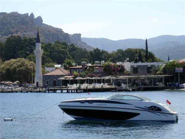 Gundogan beach and mosque with motor boat, Bodrum Peninsula Turkey