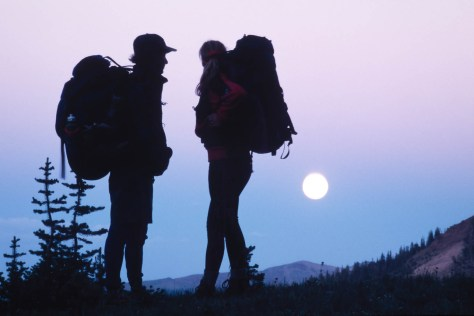 Backpacking couple watching the moonrise