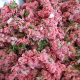 Mixing ground meat, chopped parsley, onions, and tomatoes