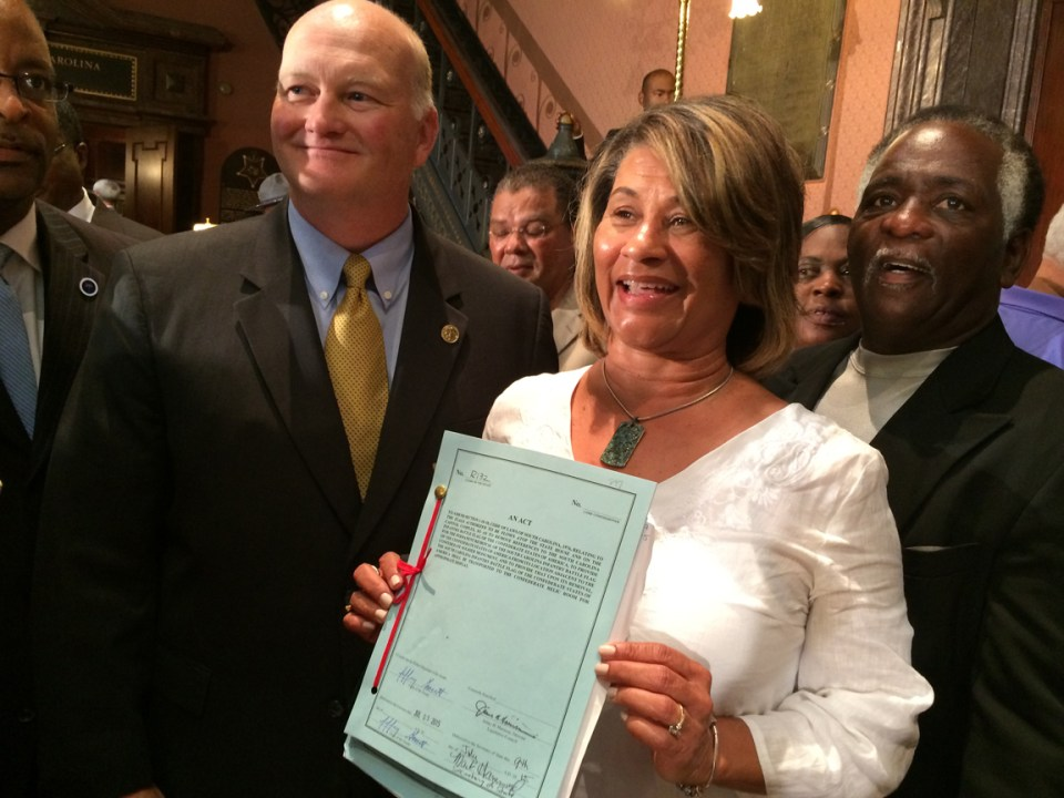 I believe this is Wanda Bailey, Strom Thurmond's granddaughter, holding the bill after the signing. A bunch of people lined up to have their pictures taken with it and Secretary of State Mark Hammond, left.