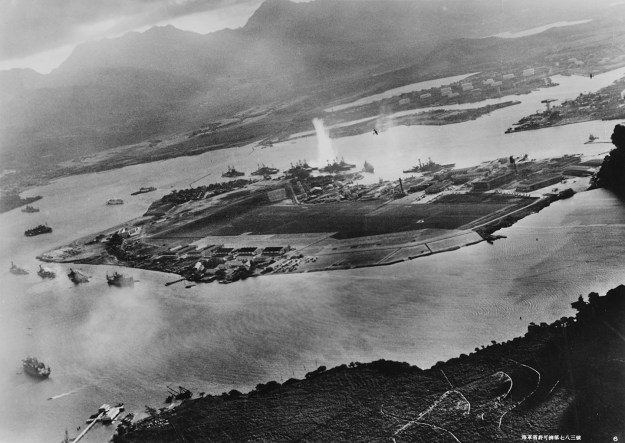 Photograph taken from a Japanese plane during the torpedo attack on ships moored on both sides of Ford Island. View looks about east, with the supply depot, submarine base and fuel tank farm in the right center distance. A torpedo has just hit USS West Virginia on the far side of Ford Island (center). Other battleships moored nearby are (from left): Nevada, Arizona, Tennessee (inboard of West Virginia), Oklahoma (torpedoed and listing) alongside Maryland, and California. On the near side of Ford Island, to the left, are light cruisers Detroit and Raleigh, target and training ship Utah and seaplane tender Tangier. Raleigh and Utah have been torpedoed, and Utah is listing sharply to port. Japanese planes are visible in the right center (over Ford Island) and over the Navy Yard at right. Japanese writing in the lower right states that the photograph was reproduced by authorization of the Navy Ministry.  U.S. Naval History and Heritage Command Photograph.