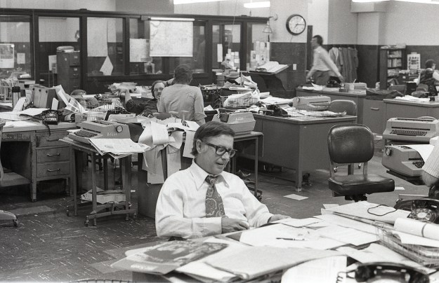 The sardonic Managing Editor Bill Sorrels presides at his desk in the middle of the newsroom (he had an office somewhere, too). You see Dave Hampton running somewhere in the background. Note the decor.