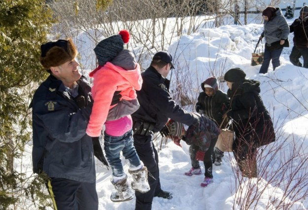 From The Washington Post: Members of the Royal Canadian Mounted Police help a family from Somalia on Feb. 17, 2017 along the U.S.-Canada border near Hemmingford, Quebec. (The Canadian Press/AP)